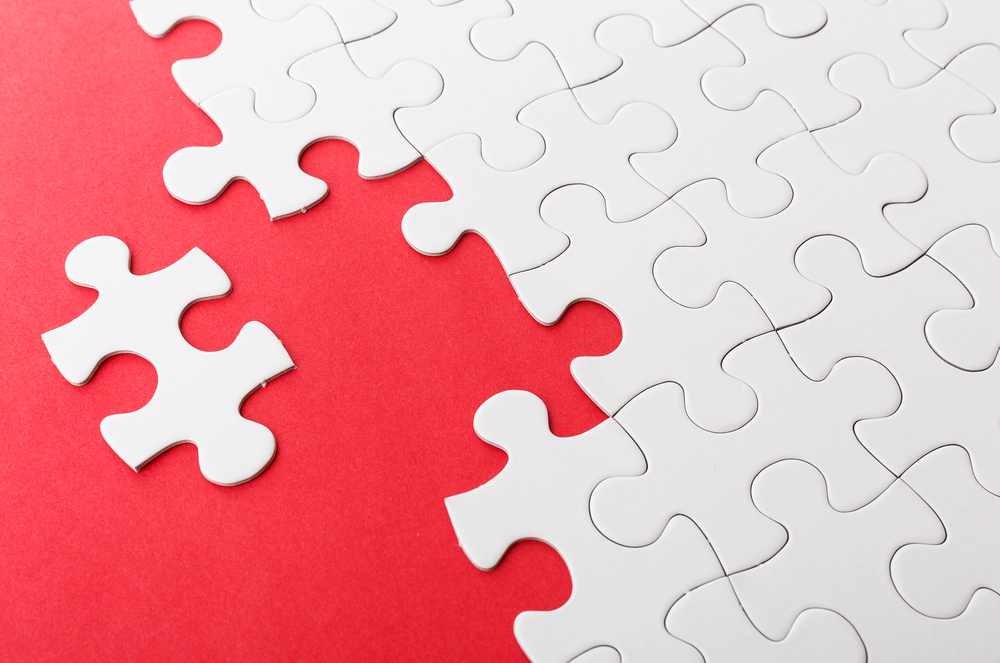 Incomplete puzzle with missing piece over red background